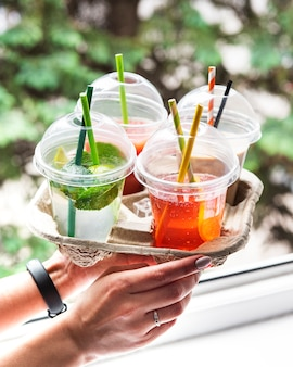 Various summer cold drinks and cocktails in a paper holder in women's hands