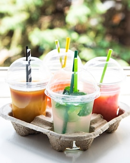 Various summer cold drinks and cocktails in a paper holder