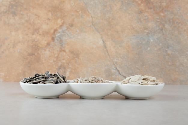 Vari semi di girasoli in ciotole bianche