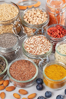 Various superfoods goji berries, quinoa, chia, hemp seeds, flax seeds, chickpeas, oats, almond, blueberries, curcuma, matcha and lantils. vegan, vegetarian healthy eating diet organic products concept