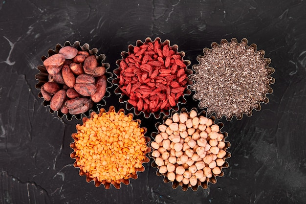Various superfoods in small bowl on black