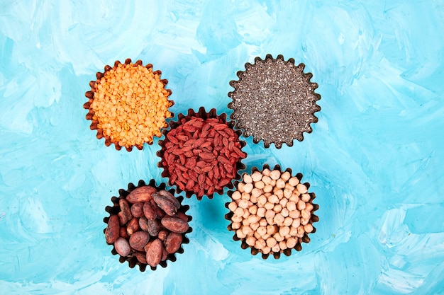 Various superfoods in small bowl on blue