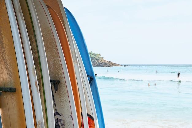 Различные доски для серфинга на песчаном пляже на фоне океана