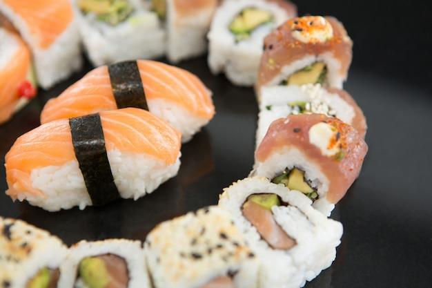 Various sushi on black table