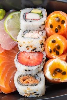 Различные суши на тарелке на столе - деталь