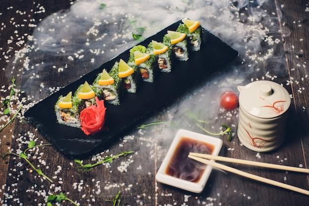 Различные суши на белом фоне с палочками на деревянных фоне.