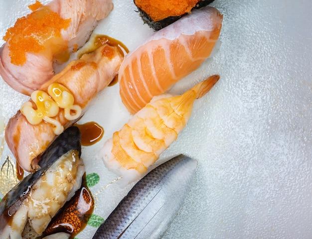 Различные суши или японская еда на белой поверхности