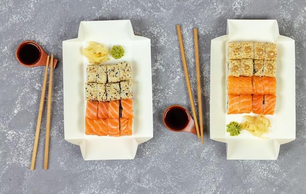 灰色の石の背景に白いエコ紙包装トレイでさまざまな寿司の選択
