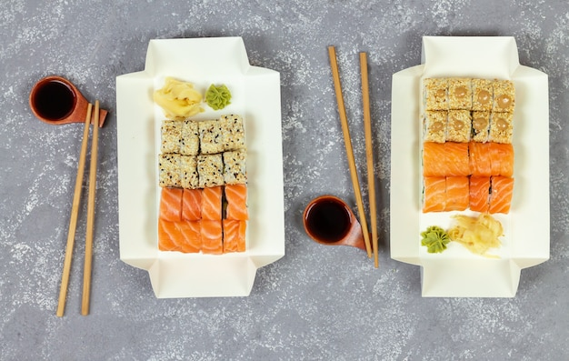 Various sushi selection in white eco paper packaging tray on gray stone background