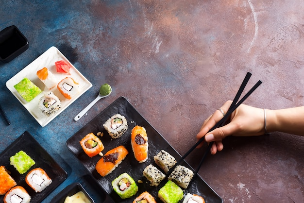 Various sushi set on plate, hand with slate sticks, sauce on stone background