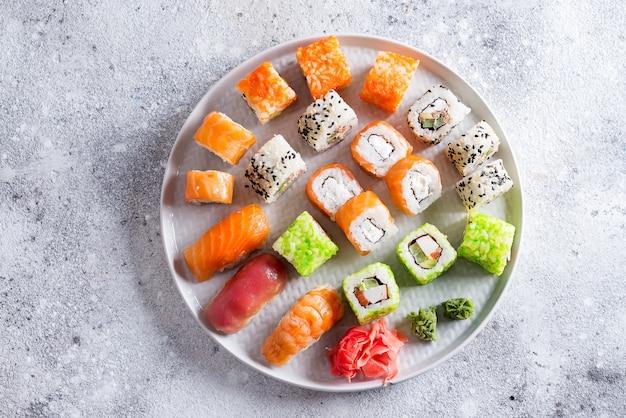 Various sushi set on plate on light stone background , flat lay