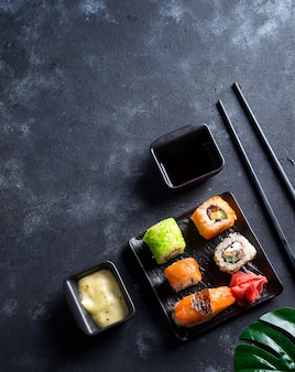 Various sushi set on plate with slate sticks, sauce on duotone stone