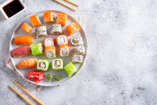 Various sushi set on plate with wooden sticks, sauce on light stone background