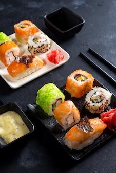 Various sushi set on slate with slate sticks, sauce and nori on black