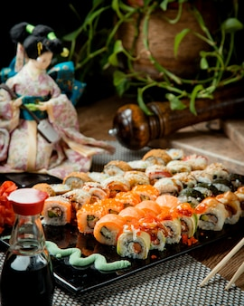 Various sushi on a tray with wasabi and soy sauce