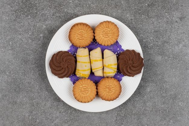 Различное сладкое печенье на белой тарелке.