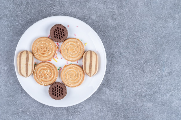 Various sweet biscuits on white plate