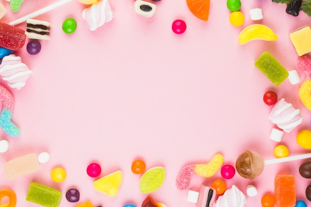 Various sweet candies forming frame on pink background