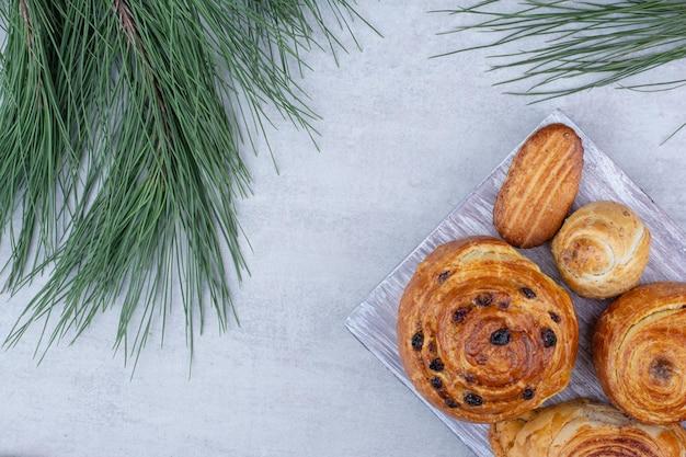 木の板にクッキーが付いた様々な甘いペストリーとロールパン。高品質の写真