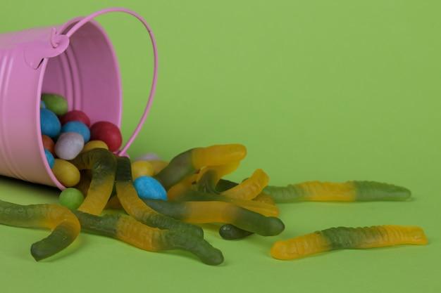 バケツの中の様々なお菓子とチョコレートとワーム。ハロウィーンの休日のコンセプト