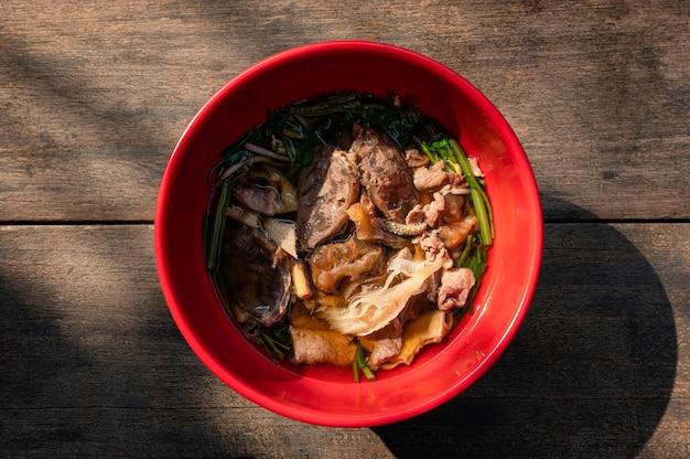 Различный тайский суп из говядины с овощами в миске на деревянном столе