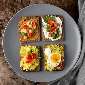 Various toasts with veggie cream flat lay