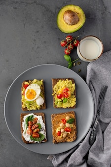 Various toasts with veggie cream on plate