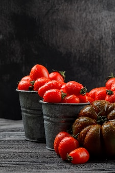 Various tomatoes in mini buckets on grey wooden and dark wall, side view.