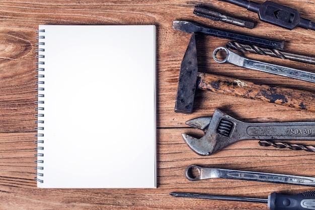 Различные инструменты и пустой блокнот на деревянном фоне