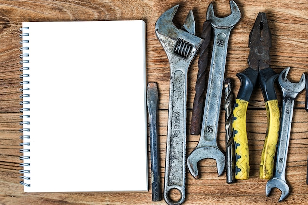 Various tools and the blank notebook on a wooden background