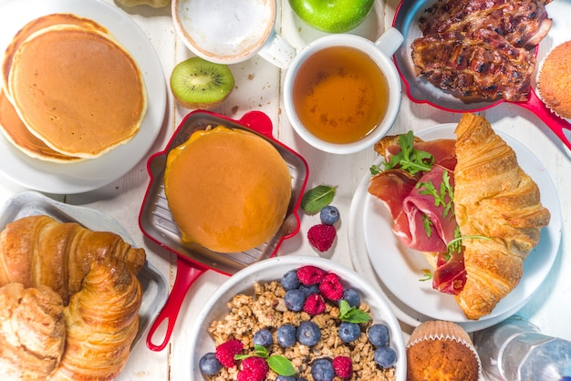 Various traditional breakfast food - fried eggs with bacon, muesli, oats, waffles, pancakes, burger, croissants, fruit berry, coffee, tea and orange juice, white table background copy space top view