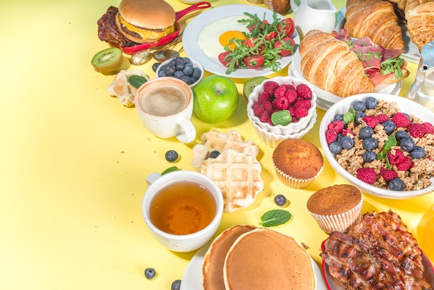 Various traditional breakfast food - fried eggs with bacon, muesli, oats, waffles, pancakes, burger, croissants, fruit berry, coffee, tea and orange juice, yellow table background copy space top view