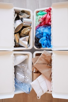 Various trash items stored by material type and ready for recycling, waste sorting concept