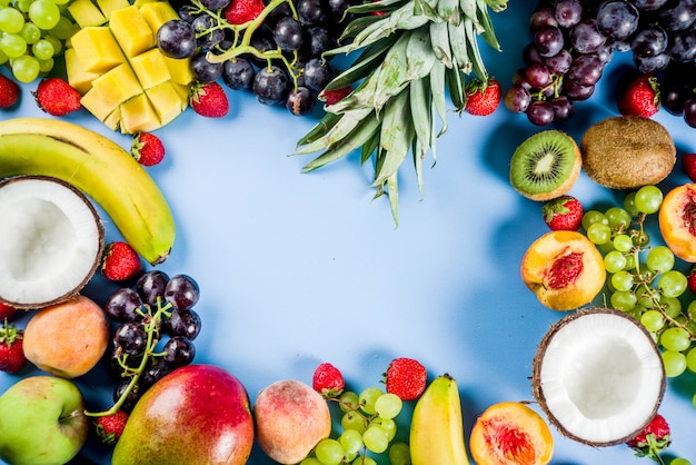 Various tropic fruits summer vitamins concept coconut pineapple grapes peach nectarine strawberry apples mango banana. top view copy space