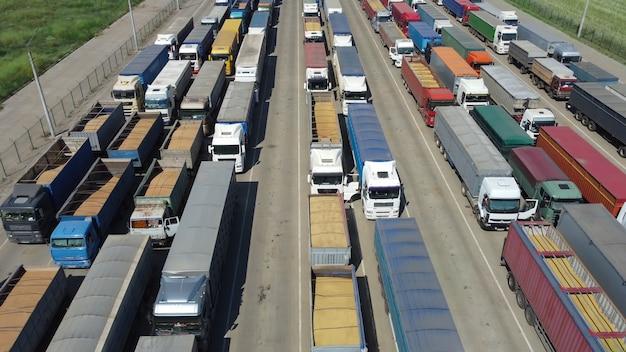 На стоянке в ожидании разгрузки стоят разные грузовики. логистика для перевозки сельхозпродукции.