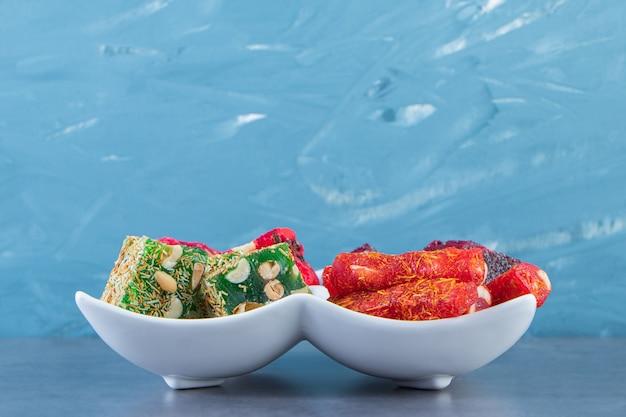 Различные рахат-лукумы на блюде на мраморной поверхности