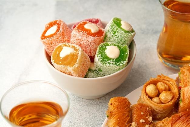 Различные турецкие сладости и чашка чая на белом текстурированном фоне