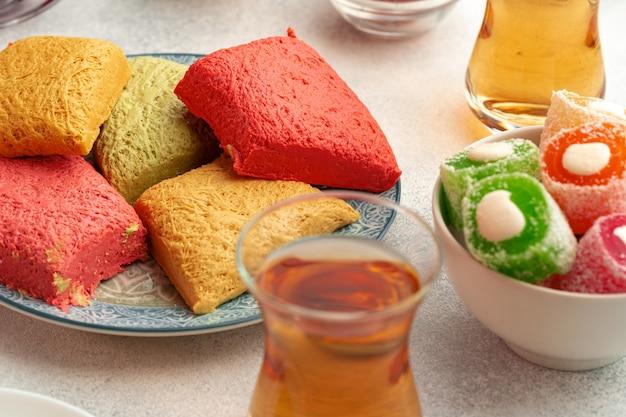 흰색 질감 배경에 다양한 터키 과자와 차 한 잔