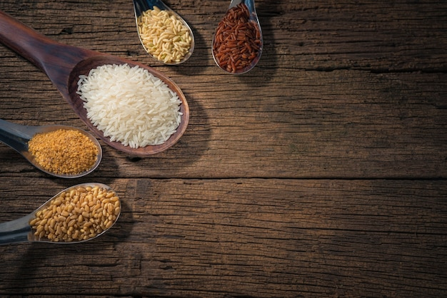 Various type of cereal grains (wheat, rice,brown rice, buckwheat, barley, black sesame,millet, lotus seeds,job's tears).various raw uncooked grains on wood background.
