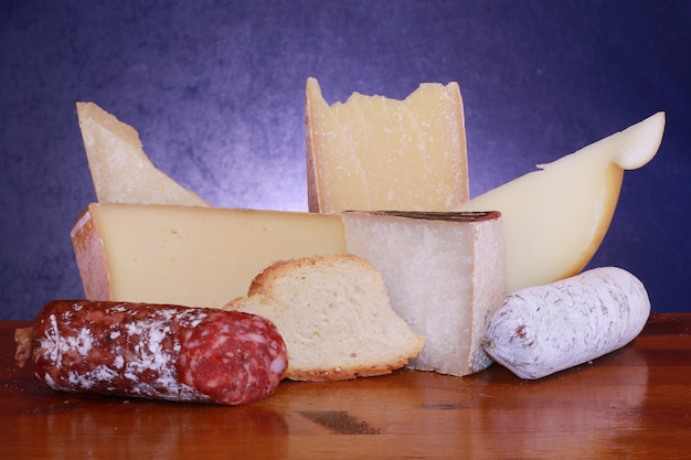 Various type of cheese and salami on wood