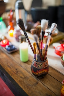 Various type of chinese paint brushes in holder over the wooden table with lighted candles