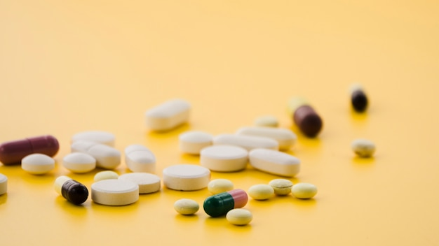 Various type of colorful pills on yellow background