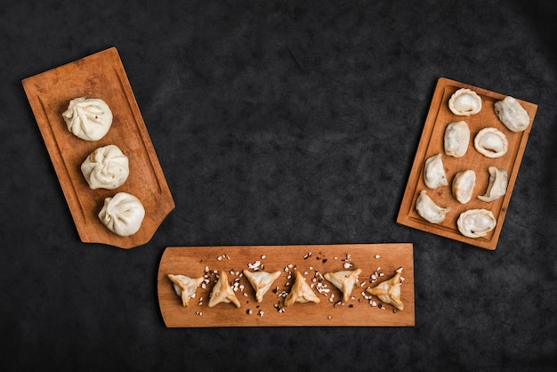 Various type of dumplings on wooden tray against black textured backdrop