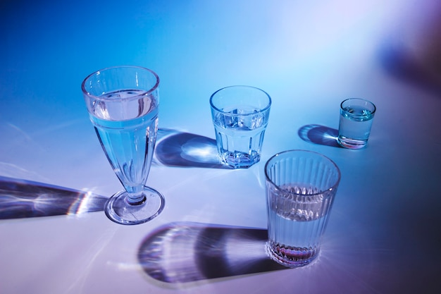Various type of glasses with drinks on blue background