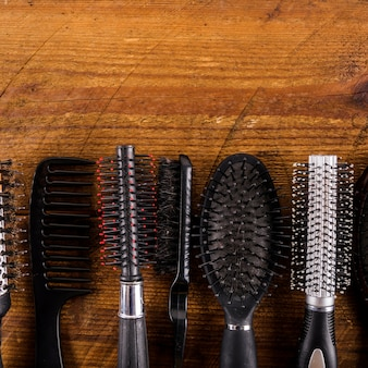 Various type of hair combs on wooden background