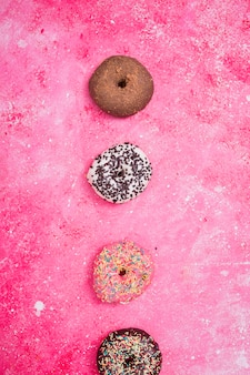 Various type of macaroons over the pink textured backdrop