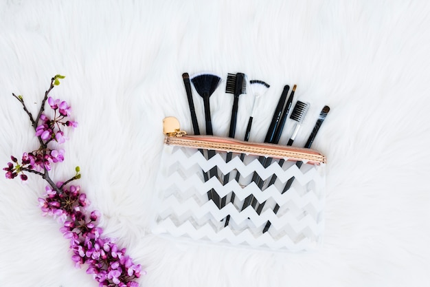 Various type of makeup brushes in plastic transparent bag with purple flower twig on white fur