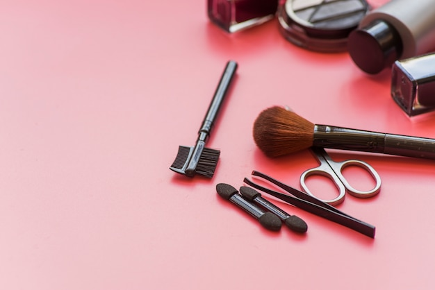Various type of makeup brushes; scissor and cosmetics product on pink background