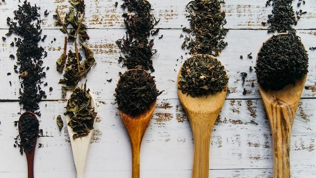 白い木製の机の上の木のスプーンでお茶のハーブの様々なタイプ