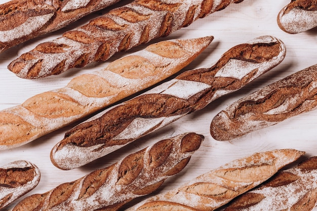 Various types of bakery bread - fresh rustic crusty loaves of bread and baguette on white background.